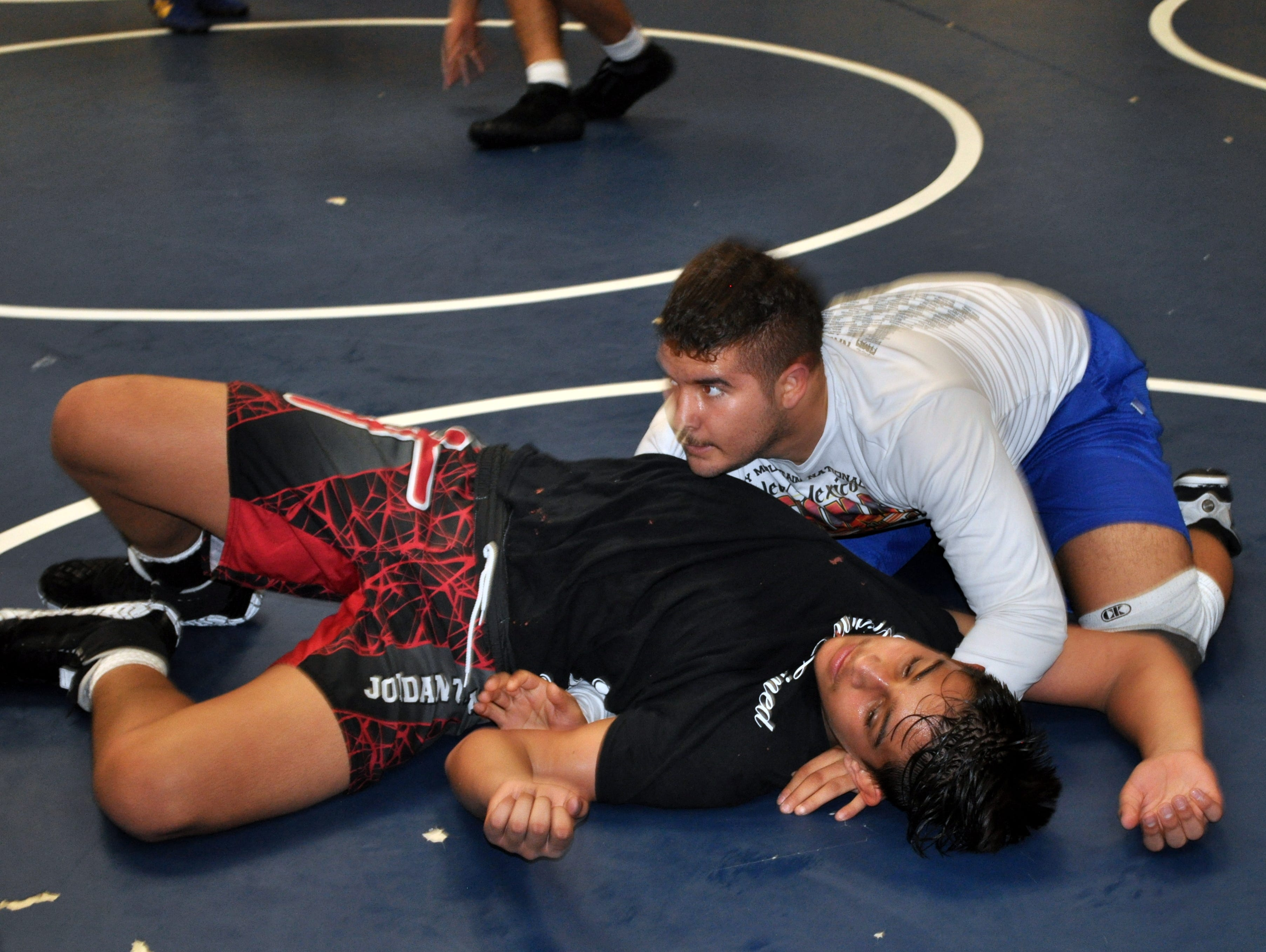 RJ Baca (top) and Jake Fuentes (bottom) get in mat work during Tuesday's practice.