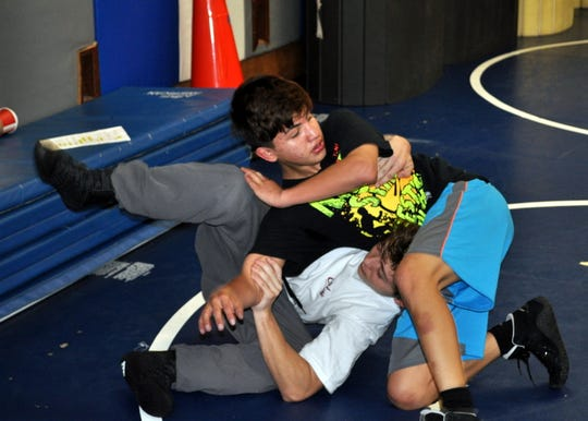 Marcus Najera (top) and Bridon Boujeois (bottom) get in mat work during Tuesday's practice.