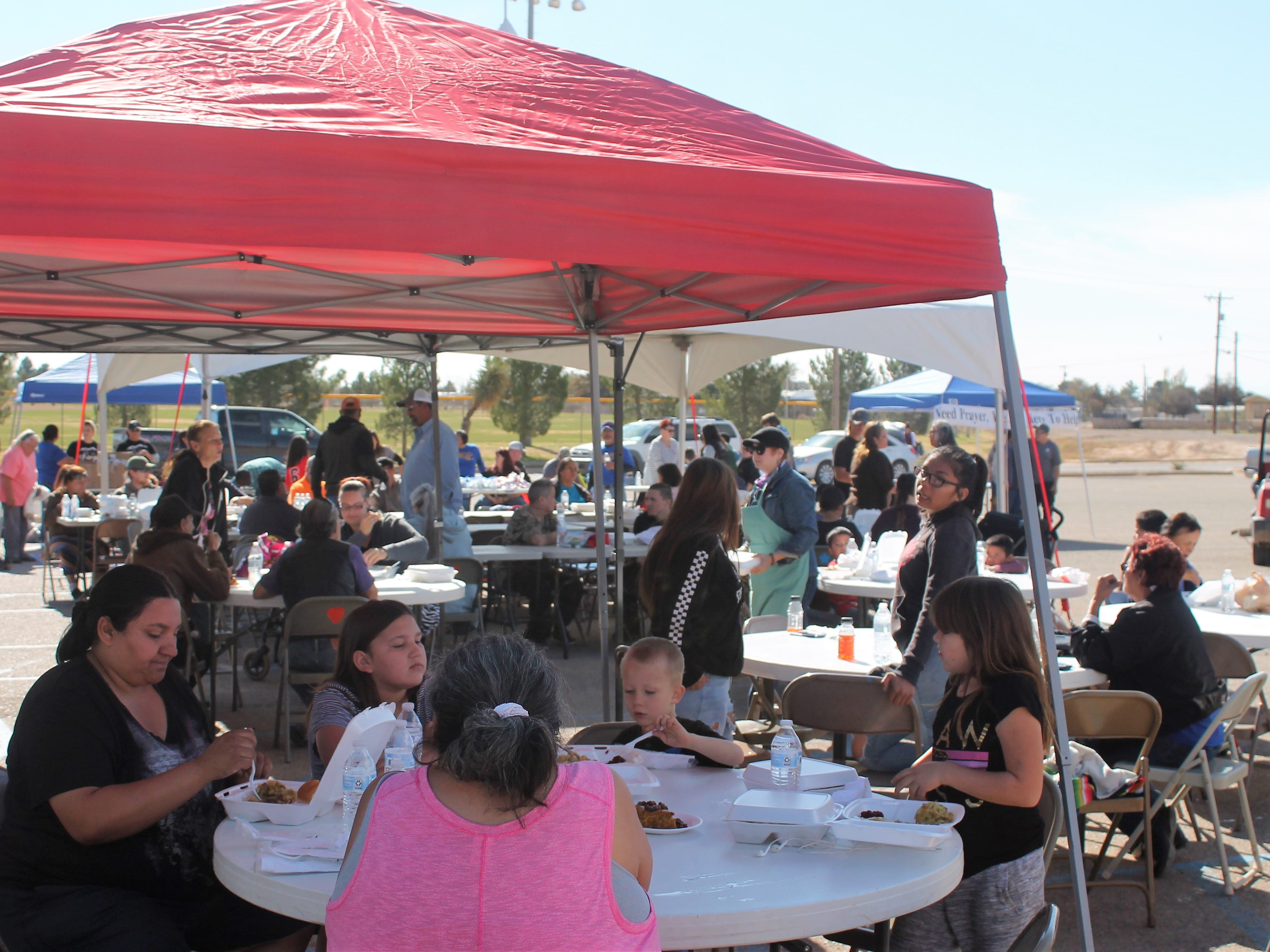 People eat a free Thanksgiving meal at the at the Mountain View Assembly of God Thanksgiving Outreach Tuesday at the Travis C. Hooser Ballfield Complex on Walker Avenue.