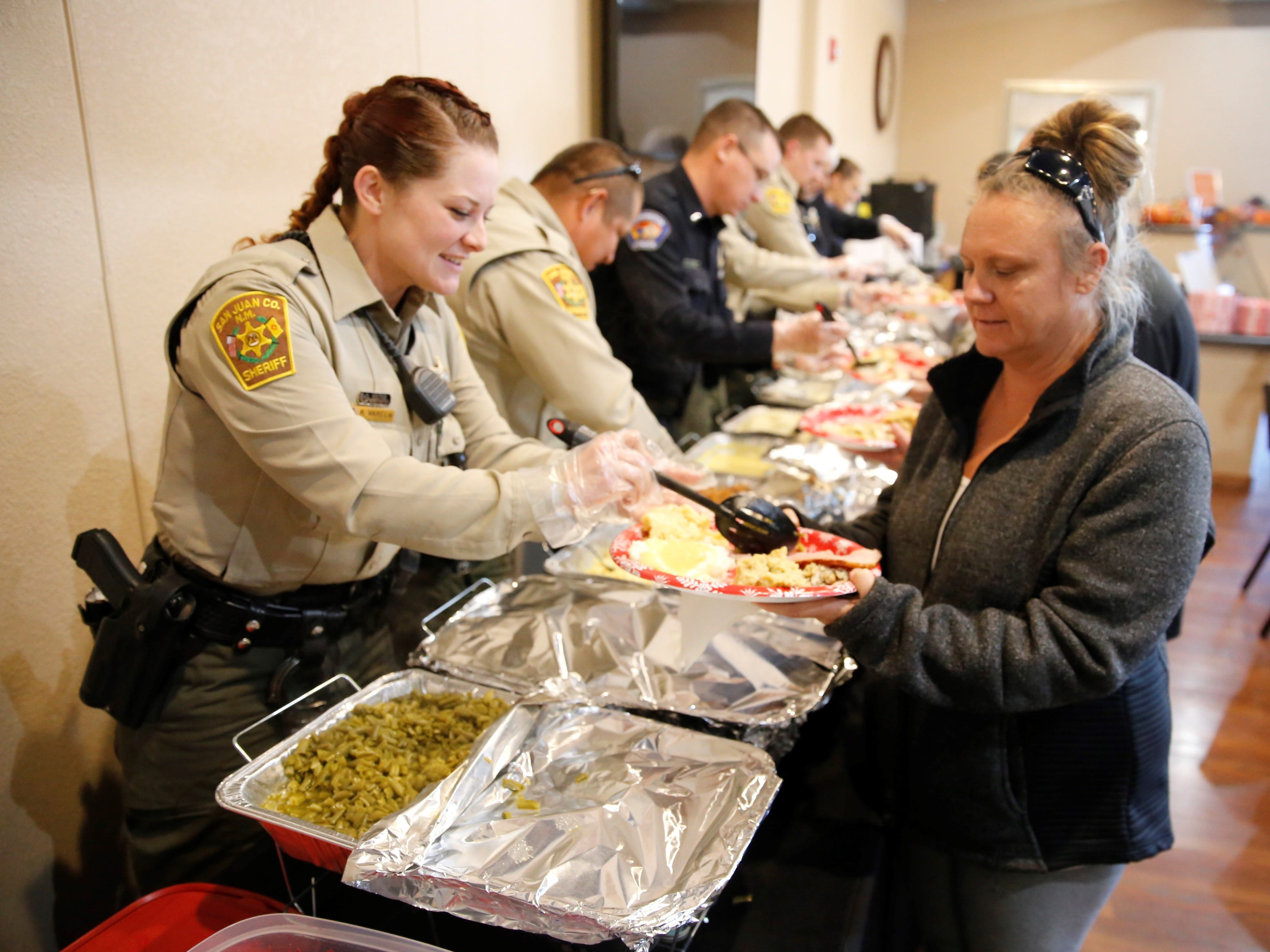 San Juan County Sheriff's Office Deputy Robin Varela, left, serves green beans to Amber Norman during a Thanksgiving meal Tuesday afternoon at Oasis Church in Farmington. The San Juan County Juvenile Services program, Desert View Family Counseling and Cottonwood Clinical Services hosted the meal.