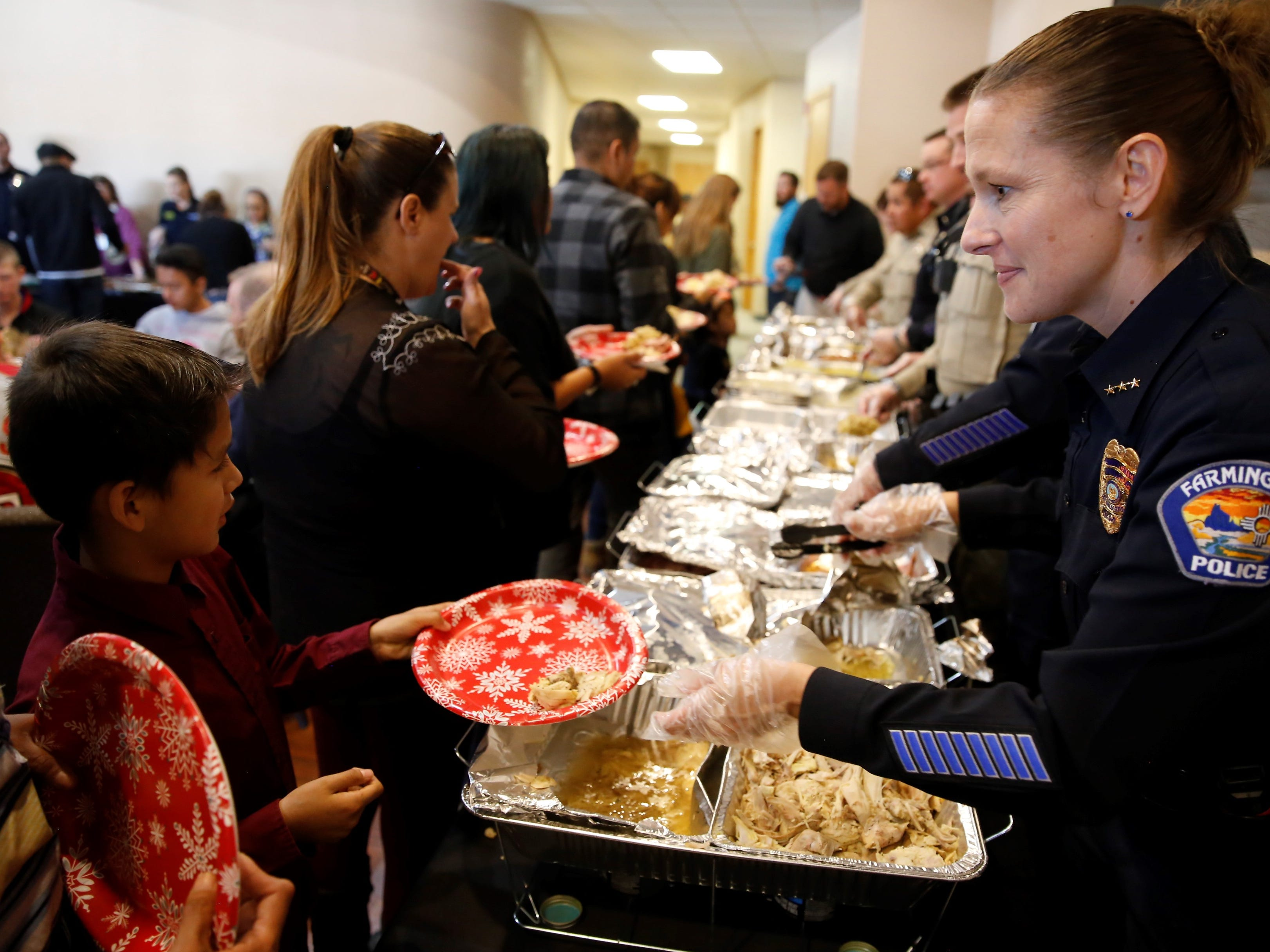 Farmington Police Department Deputy Chief Jessica Tyler, right, serves turkey to Malachi Lopez as part of a Thanksgiving meal Tuesday afternoon at Oasis Church in Farmington. The San Juan County Juvenile Services program, Desert View Family Counseling and Cottonwood Clinical Services hosted the meal.