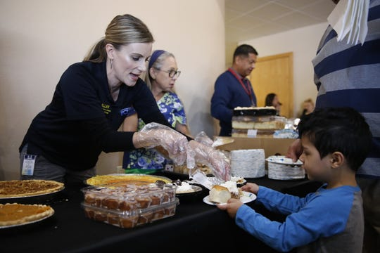 Farmington Police Department Spokesperson Georgette Allen serves pie to Giovanni Tarango during a Thanksgiving meal Tuesday afternoon at Oasis Church in Farmington. The San Juan County Juvenile Services program, Desert View Family Counseling and Cottonwood Clinical Services hosted the meal.