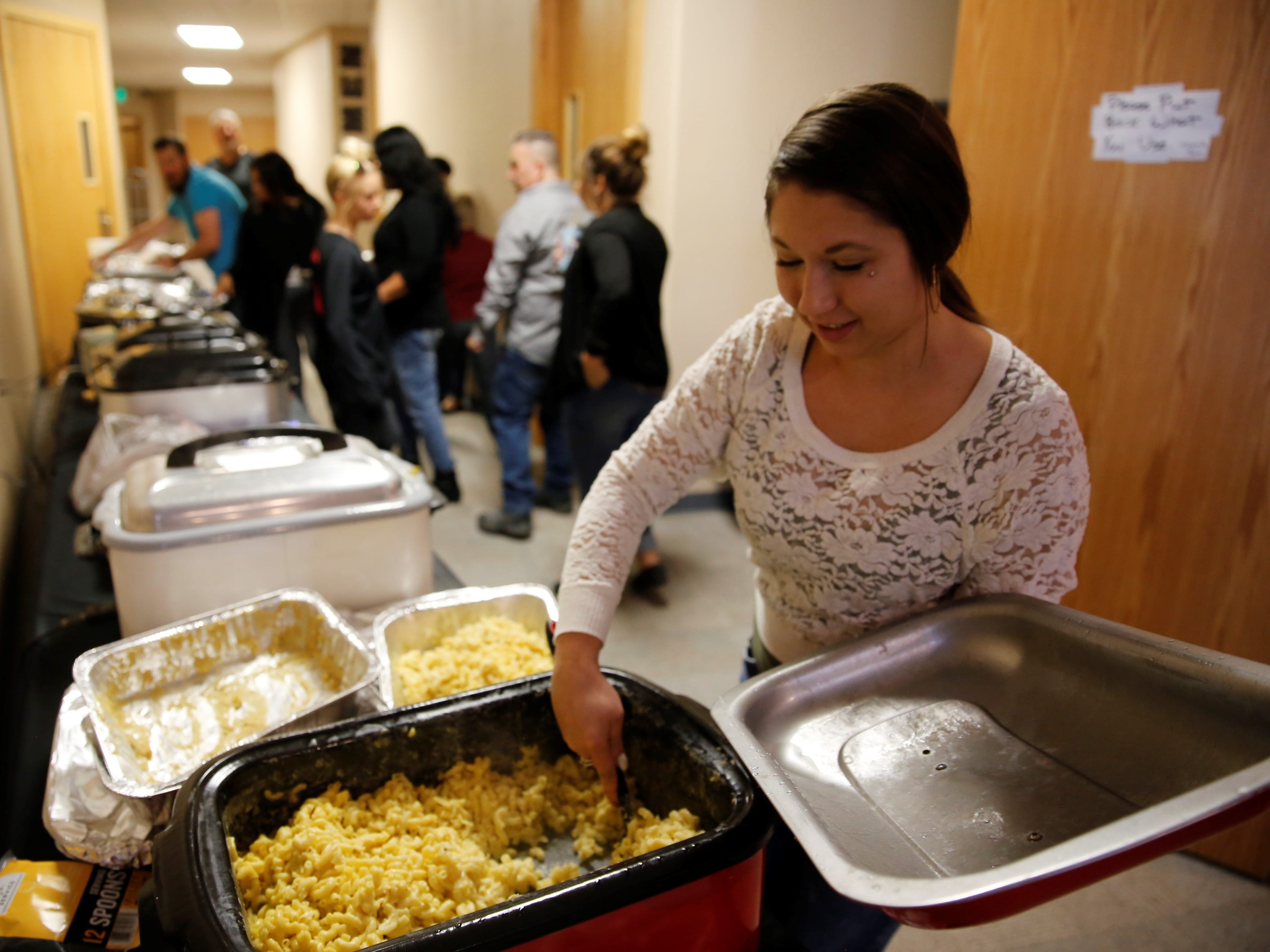 Maleia Osborne dishes out macaroni and cheese to be served during a Thanksgiving meal Tuesday afternoon at Oasis Church in Farmington. The San Juan County Juvenile Services program, Desert View Family Counseling and Cottonwood Clinical Services hosted the meal.