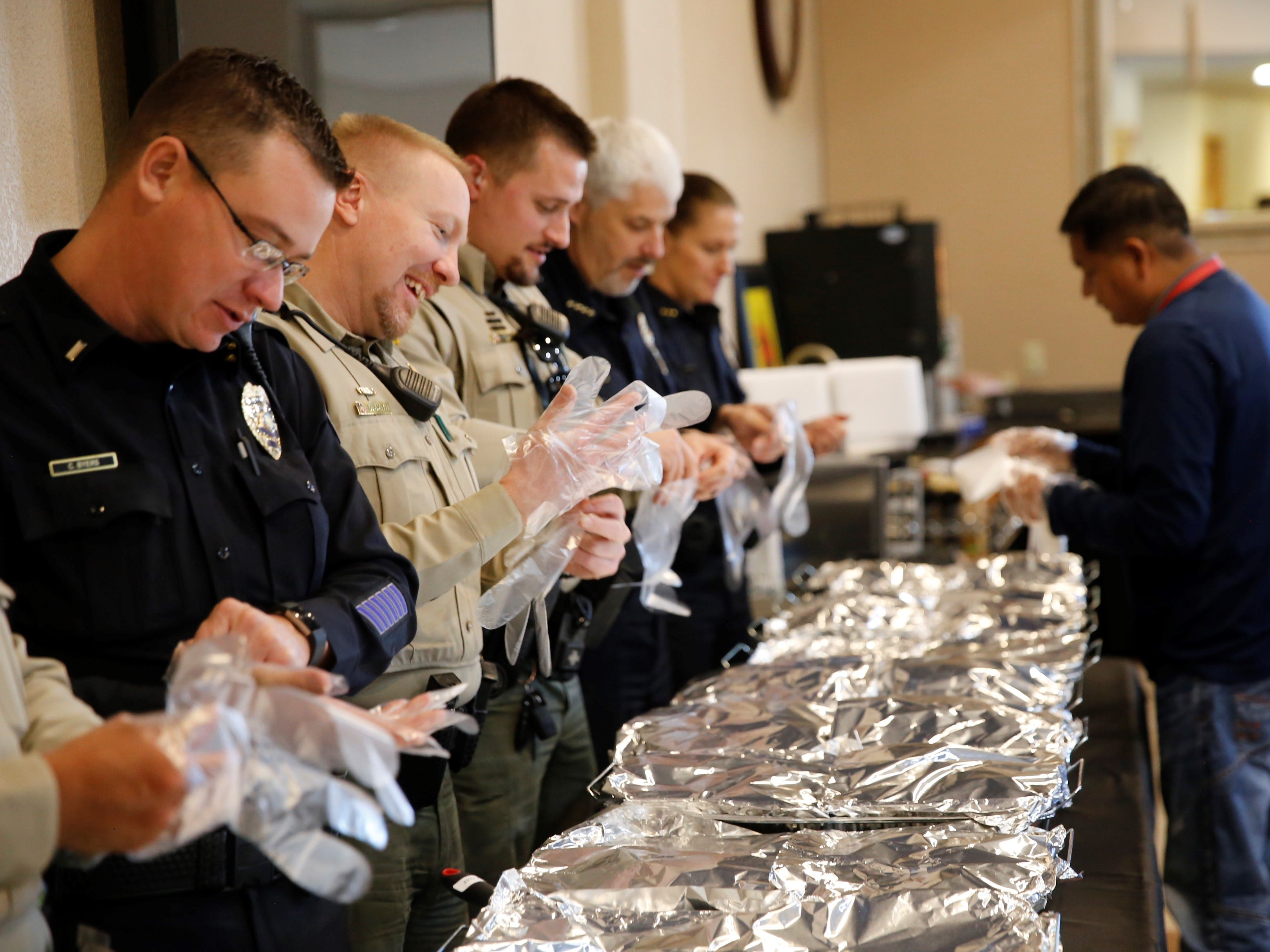 Homer Gleason, right, hands out gloves to members of the Farmington Police Department and the San Juan County Sheriff's Office who helped serve a Thanksgiving meal for the community Tuesday afternoon at the Oasis Church in Farmington. The San Juan County Juvenile Services program, Desert View Family Counseling and Cottonwood Clinical Services hosted the meal.