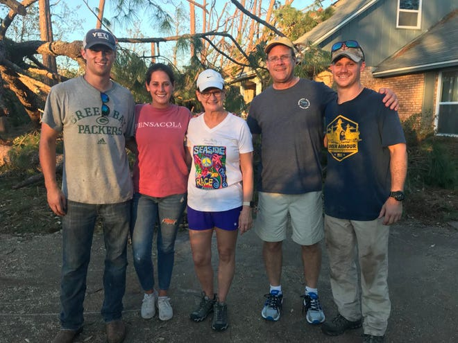"""From left, Ensign Andrew Kittel, Carolyn Gadboys, Lisa Churchwell, Gary Churchwell and Ensign Nicholas Sholty gather after a day of work removing debris, furniture, and carpet from the Churchwell home following Hurricane Michael's destruction. Ensigns Kittel and Sholty, both student aviators from the """"Red Knights"""" of Training Squadron THREE and Gadboys worked several 14-16 hour days providing assistance to nearly 100 people."""