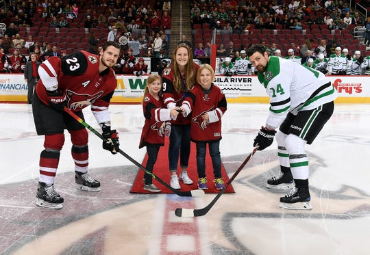 Lyndsey Fry (center), along with members of her Small Fry's program, prepare to drop the puck between Oliver Ekman-Larsson (23) and Jamie Benn (14) before a game between the Arizona Coyotes and Dallas Stars at Gila River Arena on February 1, 2018 in Glendale, Arizona.