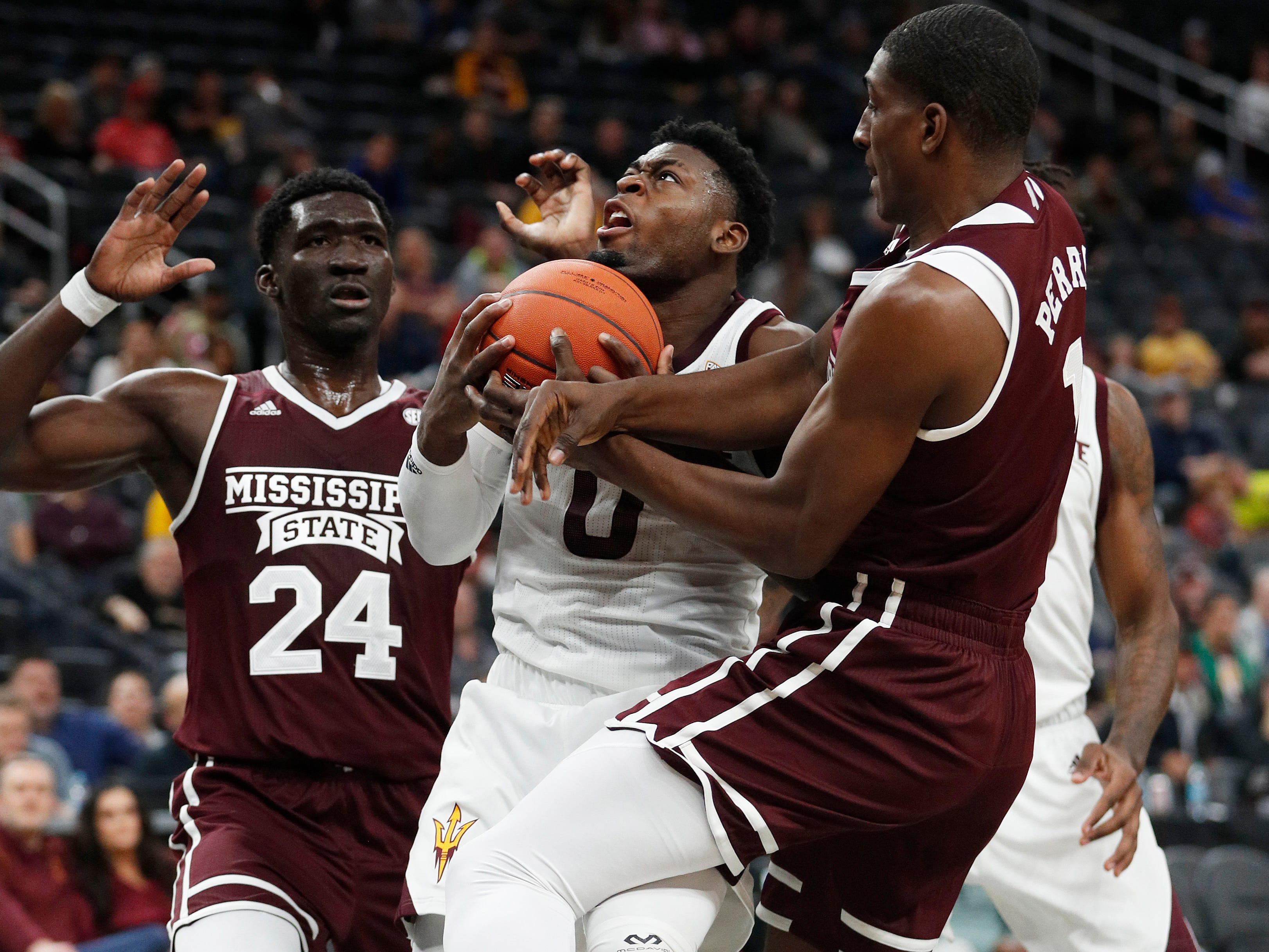 Arizona State's Luguentz Dort (0) drives through Mississippi State's Abdul Ado (24) and Reggie Perry during the first half of a NCAA college basketball game Monday, Nov. 19, 2018, in Las Vegas. (AP Photo/John Locher)