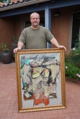 "David Van Auker of Silver City New Mexico is shown in August 2017 with the ""Woman-Ochre,"" a masterpiece by the artist Willem de Kooning. Van Auker inadvertently purchased the painting as part of an estate sale and later discovered it had been stolen from the University of Arizona 31 years earlier."