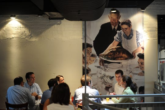"America Eats Tavern in Washington, D.C. features a print of the Norman Rockwell painting ""Freedom from Want."""