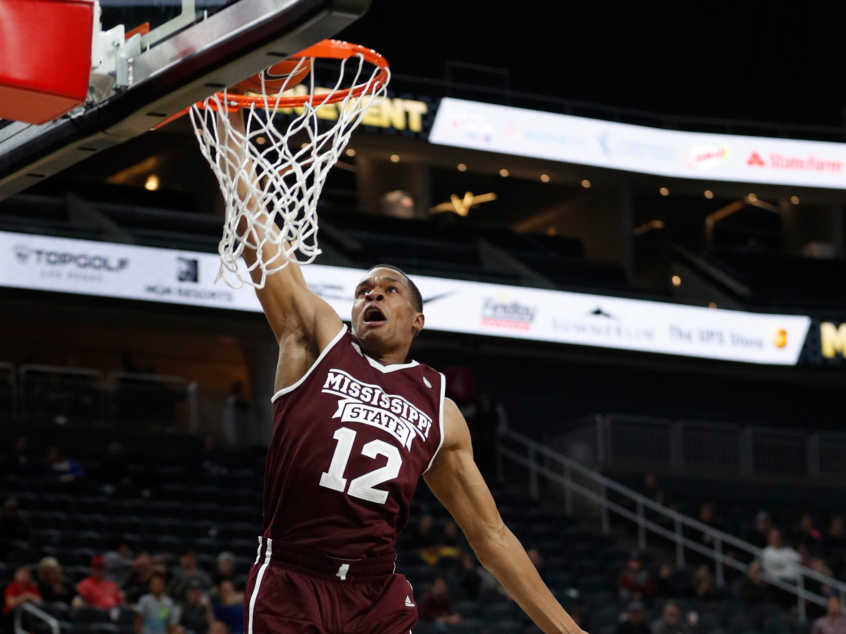 Mississippi State's Robert Woodard II (12) dunks over Arizona State's Taeshon Cherry (35) during the second half of an NCAA college basketball game, Monday, Nov. 19, 2018, in Las Vegas. Arizona State won 72-67.