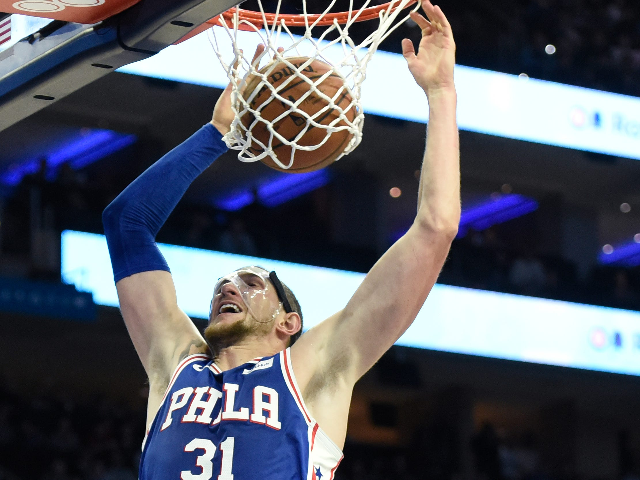 Philadelphia 76ers' Mike Muscala (31) dunks the ball as Phoenix Suns' TJ Warren (12) looks on in second half of an NBA basketball game, Monday, Nov. 19, 2018, in Philadelphia. The 76ers beat the Suns 119-114. (AP Photo/Michael Perez)