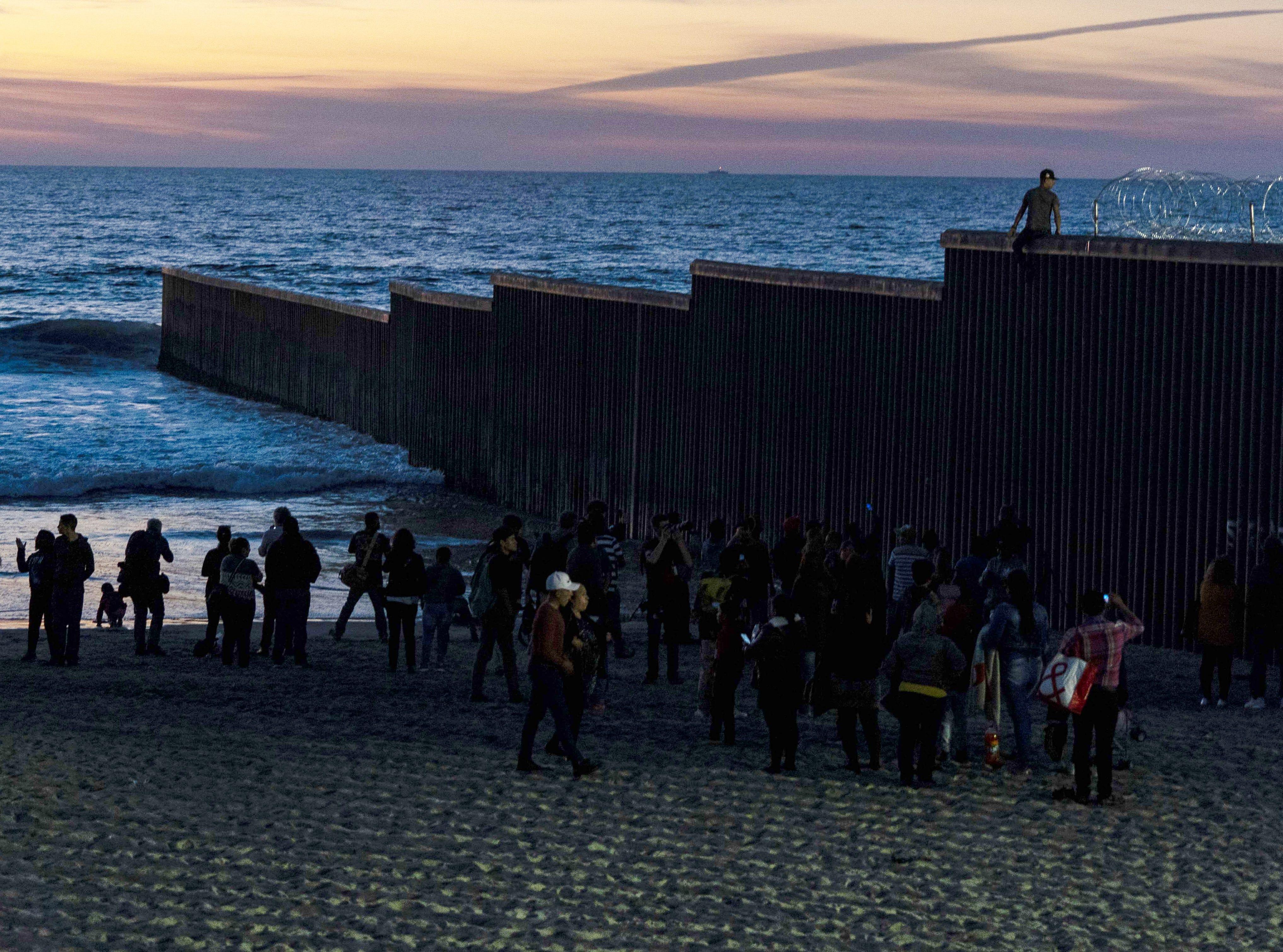Man tries to climb over atop the U.S.-Mexico border fence on Nov. 18, 2018, at Playas de Tijuana, Mexico.