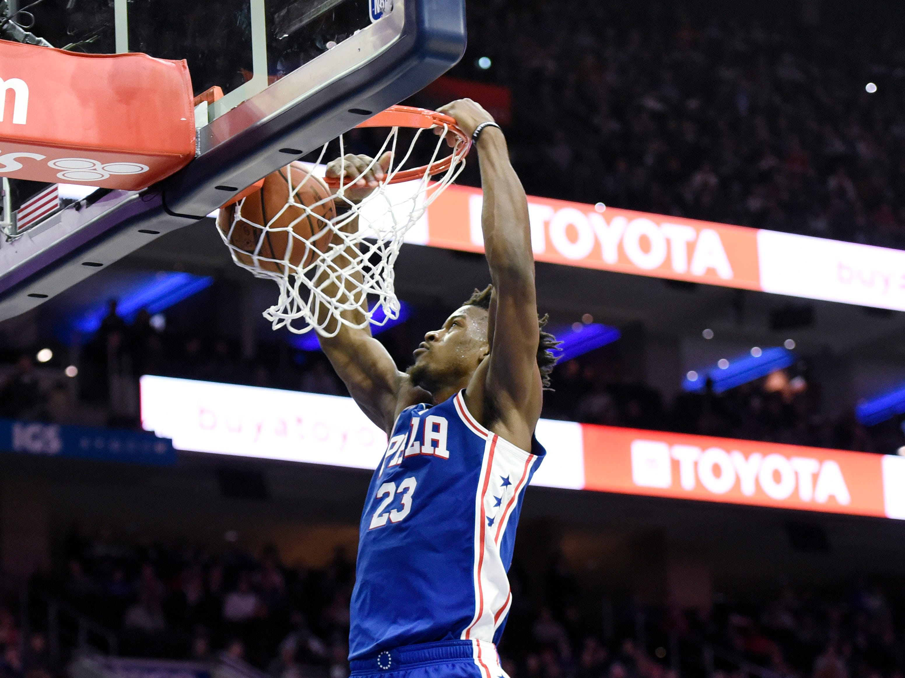 Philadelphia 76ers' Jimmy Butler (23) dunks the ball as Phoenix Suns' Trevor Ariza (3) looks on in the second half of an NBA basketball game, Monday, Nov. 19, 2018, in Philadelphia. The 76ers beat the Suns 119-114.