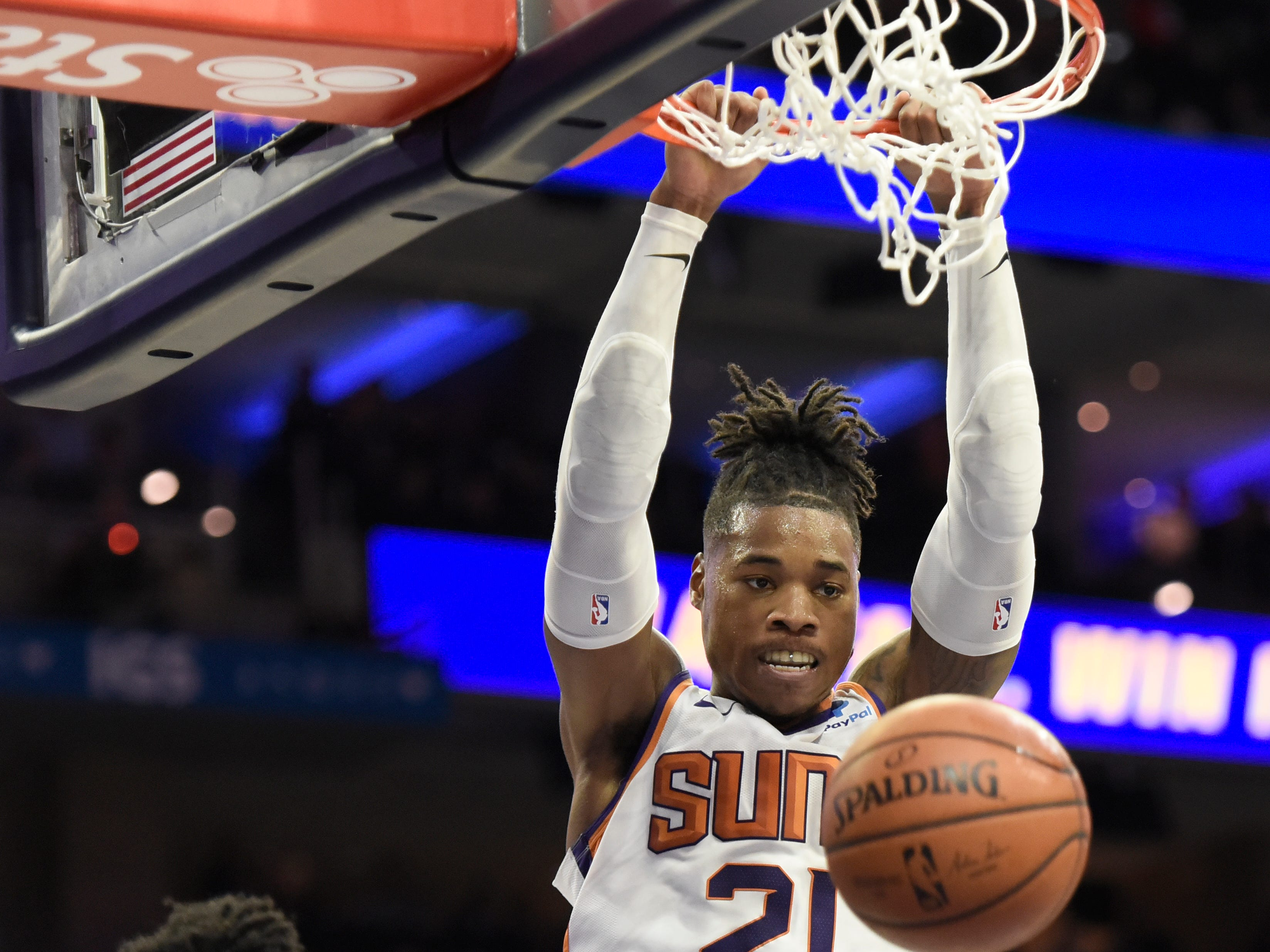 Phoenix Suns' Richaun Holmes (21) dunks the ball over Philadelphia 76ers' Joel Embiid (21) in the first half of an NBA basketball game, Monday, Nov. 19, 2018, in Philadelphia. (AP Photo/Michael Perez)