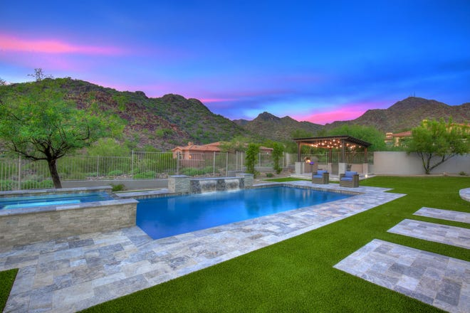 The backyard has a pergola, barbecue station, pool/spa and McDowell mountain views.