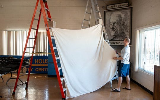 Samuel MacDonald uses two ladders, a white sheet and a bench to create a makeshift portrait studio.