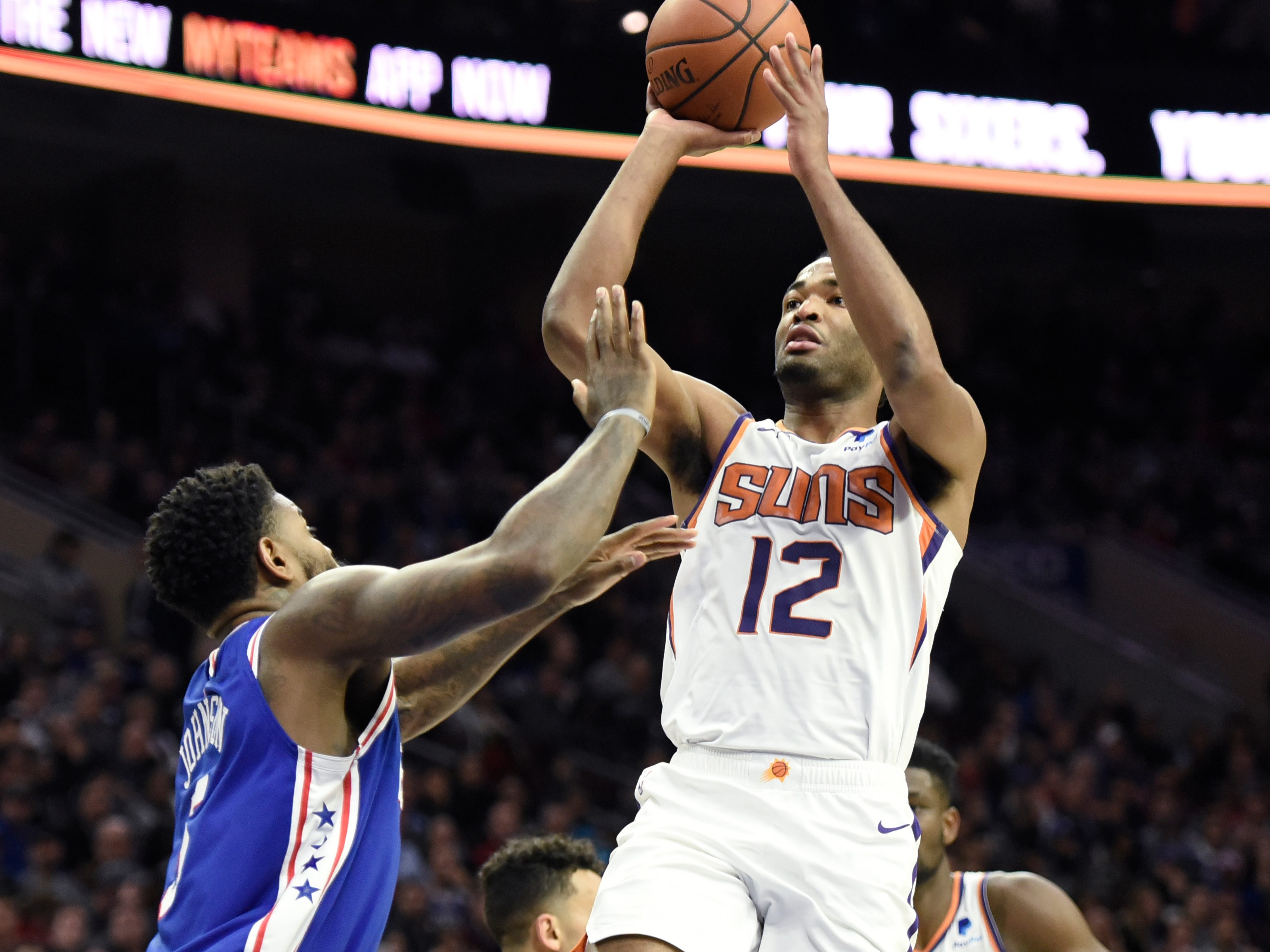 Phoenix Suns' TJ Warren (12) shoots the ball over Philadelphia 76ers' Amir Johnson in the first half of an NBA basketball game, Monday, Nov. 19, 2018, in Philadelphia.