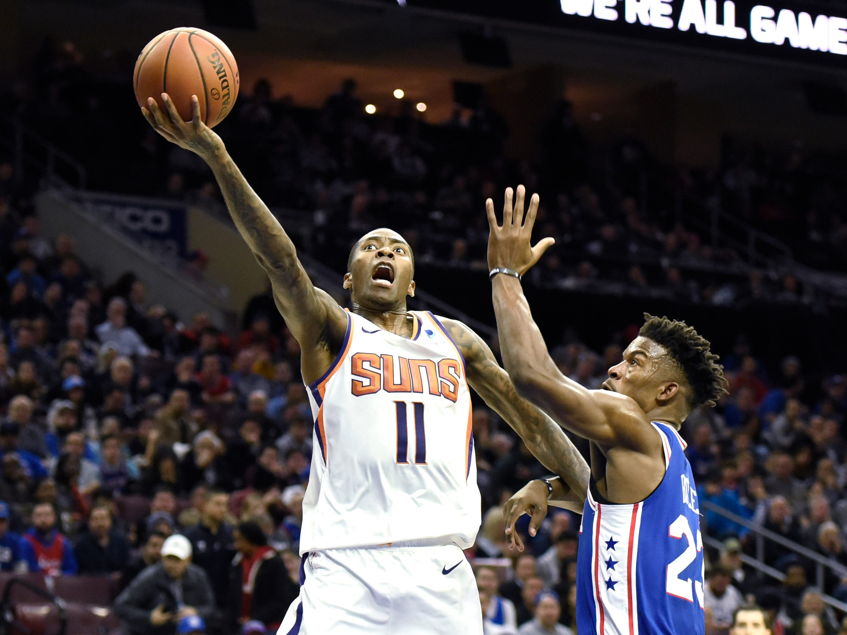 Phoenix Suns' Jamal Crawford (11) drives to the basket past Philadelphia 76ers' Jimmy Butler (23) in the first half of an NBA basketball game, Monday, Nov. 19, 2018, in Philadelphia. (AP Photo/Michael Perez)