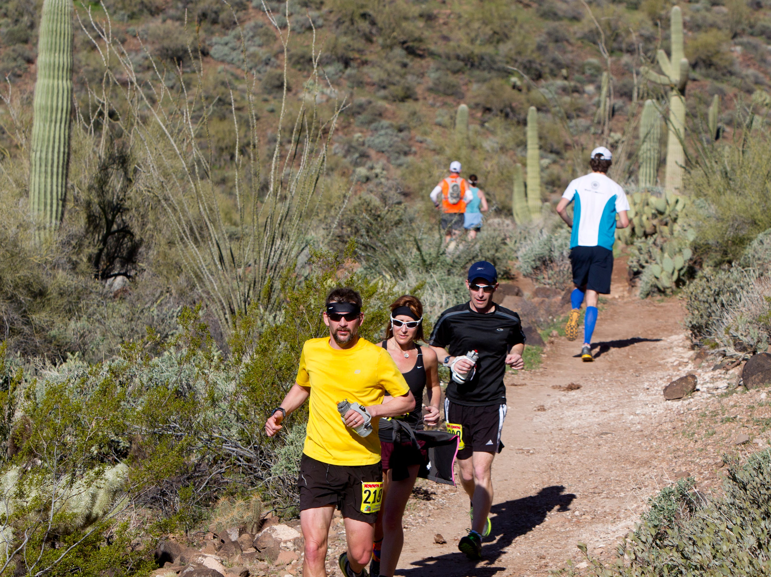 Jon Aardal, 41, of Colorado, (yellow shirt), Nadine Hamilton, 38, of Pennsylvania, and Craig Branaghan, 34, of Colorado, compete in the Aravaipa Running Elephant Mountain Desert Runner Trail Series at Cave Creek Regional Park in 2013.