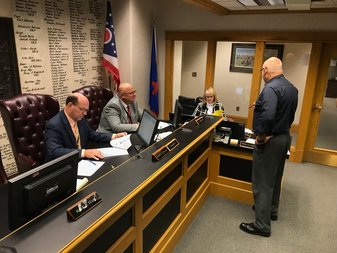 Ottawa County Commissioners Mark Coppeler and James Sass meet with Gino Monaco, right, administrator at the Ottawa County Sanitary Engineering Department.