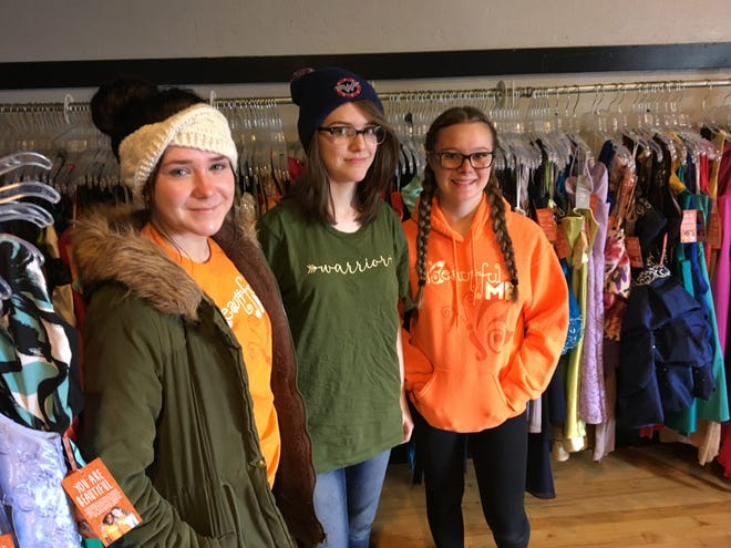 Eve Kinert, 19, left, Danni Elliott, 17, and Naomi Elliott, 14, no relation, stand beside dresses stored at the AUD in Richmond. They were three of the 10 teens to intern with A Beautiful Me over the summer and are preparing to help open A Beautiful Me Closet in downtown Port Huron.