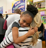 AnnaLysse Barrington, a Morse Elementary School first-grader, gets a hug during the annual Thanksgiving feast on Nov. 20, 2018.
