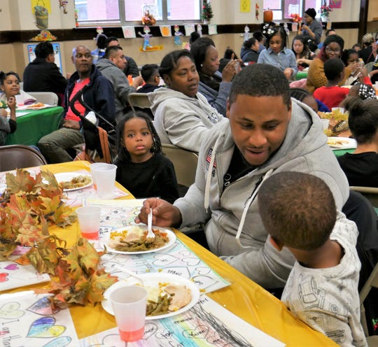 Morse Elementary School student Honor Archer, 6 (far right) talks to his dad, Eric Archer, during the school's annual Thanksgiving celebration on Nov. 20, 2018.