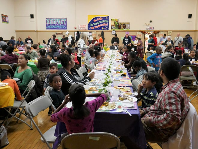 Morse Elementary School first-graders and their loved ones sit together and eat during their annual Thanksgiving celebration on Nov. 20, 2018.