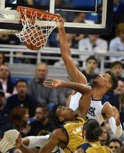 Nevada's Trey Porter dunks over California Baptist's Dejon Davis during Monday's Wolf Pack win.
