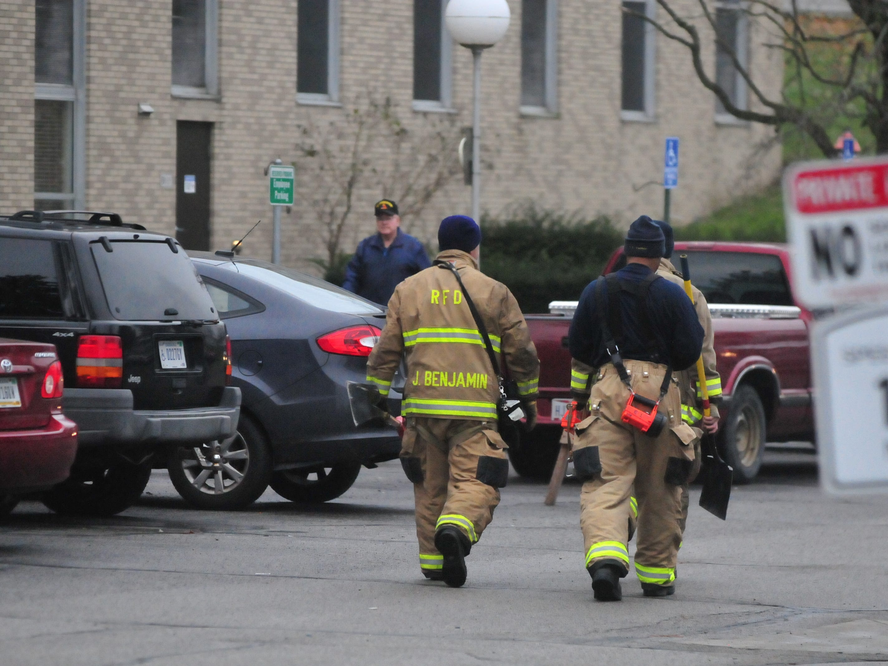 Richmond Fire Department personnel carries equipment into Interfaith Apartments on Tuesday morning to assist the investigation into Monday night's fire.