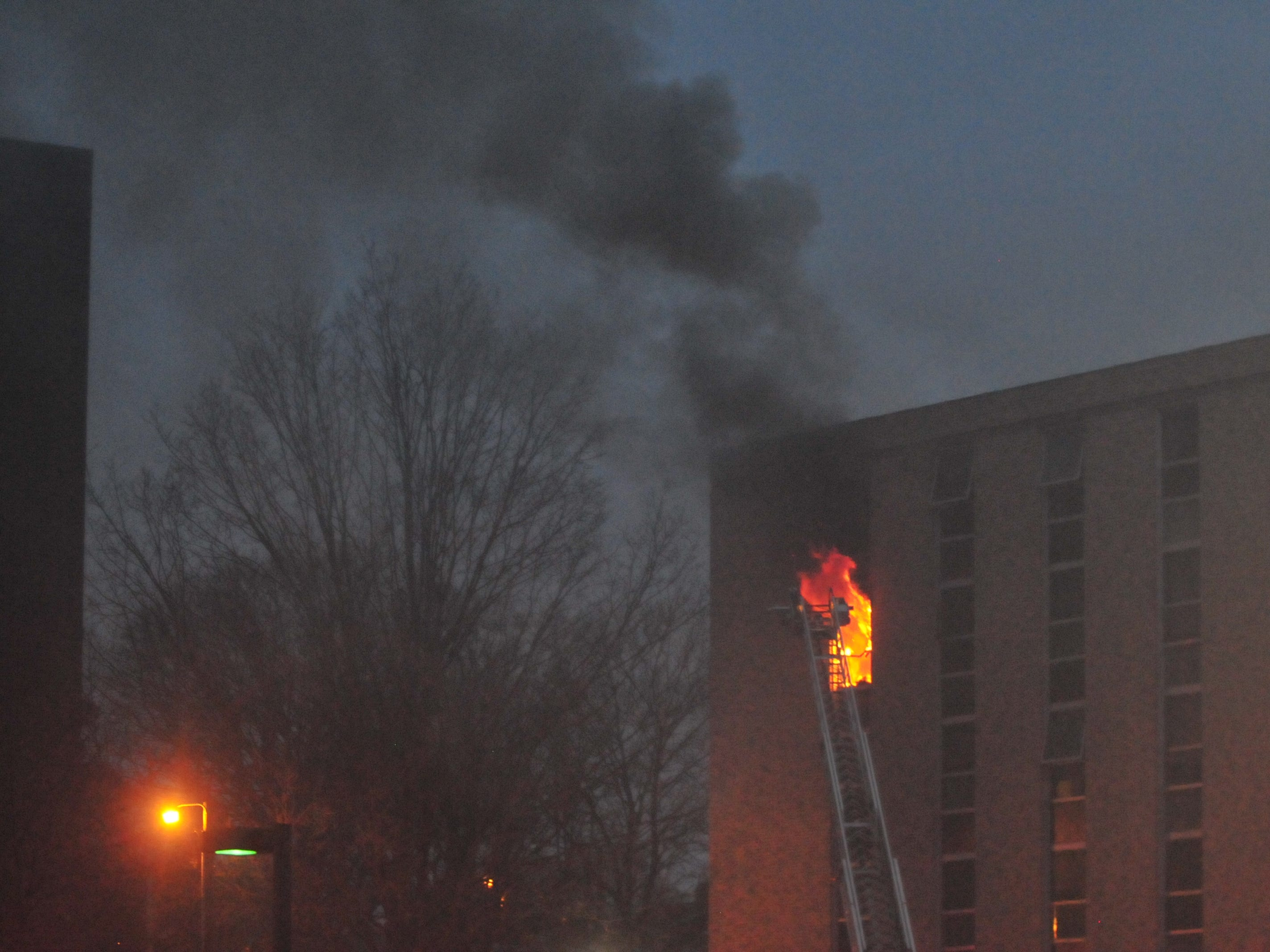 Flames erupt out of a fifth-story window at the Interfaith Apartments on Nov. 19, 2018.