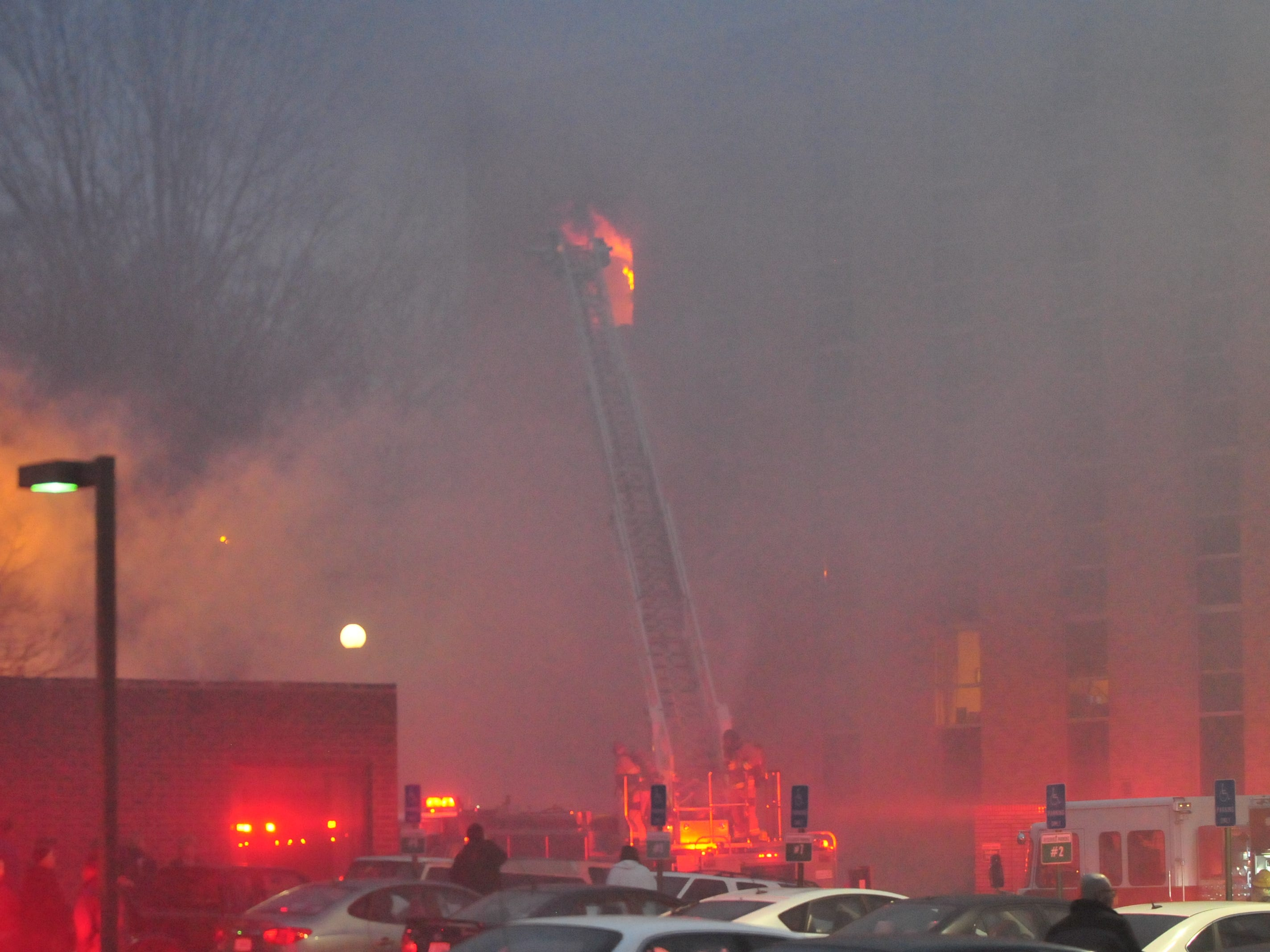 Flames erupt out of a fifth-story window at the Interfaith Apartments on Monday evening.