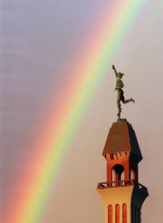 A statue of Mercury on top of the Lawyers Co-Op building downtown  appears to be reaching out for a rainbow that  made a brief appearence on Sept. 28, 1994.