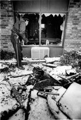 Greece police officer, the only guard on duty, looks into one of the downstairs rooms of the Greece Holiday Inn that was damaged by smoke and water. (Burr Lewis photo, 11/27/1978)