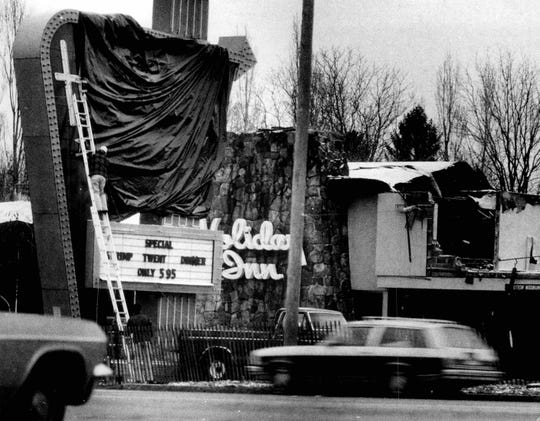 Workmen cover sign at burned out Greece Holiday Inn on West Ridge Road. (Joe Watson photo, 12/9/1978)