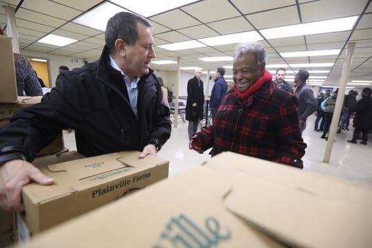 Congressman Joseph Morelle picks out a turkey for Willean Banks.