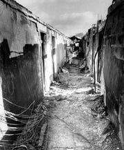 Greece Ridge Firefighter walks down burned out hall on the second floor of the Greece Holiday Inn. (Burr Lewis photo, 11/27/1978)