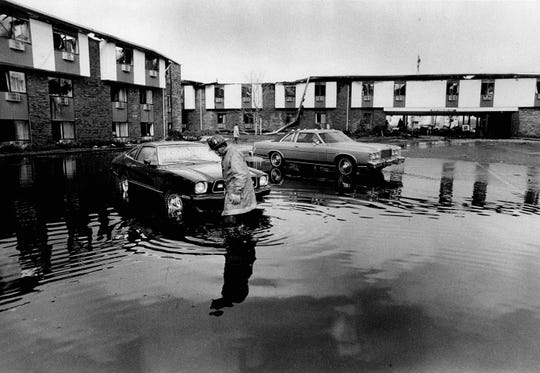 Fireman wades through water looking for drain to dispose of the excess water used for putting out the Greece Holiday Inn fire. (Peter Weinberger photo, 11/26/1978)