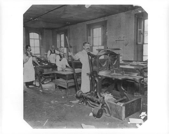Employees of Lawyers Co-operative Publishing trim pages and assemble books circa 1914.