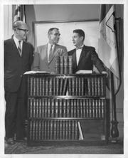 """Thomas H. Gosnell, left, president of Lawyers Cooperative Publishing, Rochester Mayor Peter Barry and Sol M. Linowitz plan the shipment of a 66-volume set of U.S. law books to Rennes, France, Rochester's """"twin"""" city, in 1959. Linowitz is chairman of the Mayor's Committee for Twinning of the Communities."""