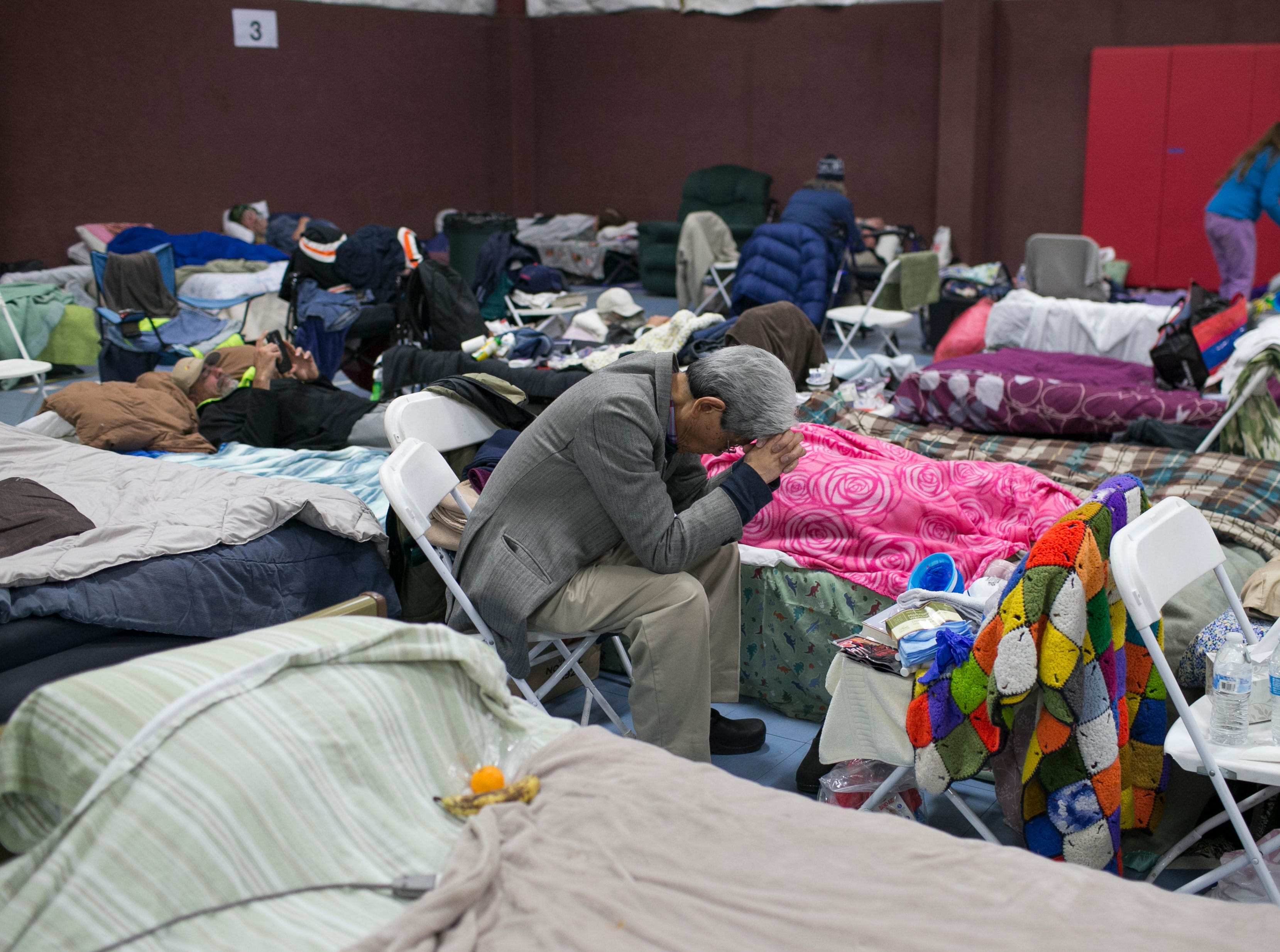 A Paradise evacuee rests with his head on his hands at the East Avenue Church Shelter in Chico, California on November 15, 2018. The shelter was full less than a week after the Camp Fire destroyed the town of Paradise, displacing thousands and killing more than 75.