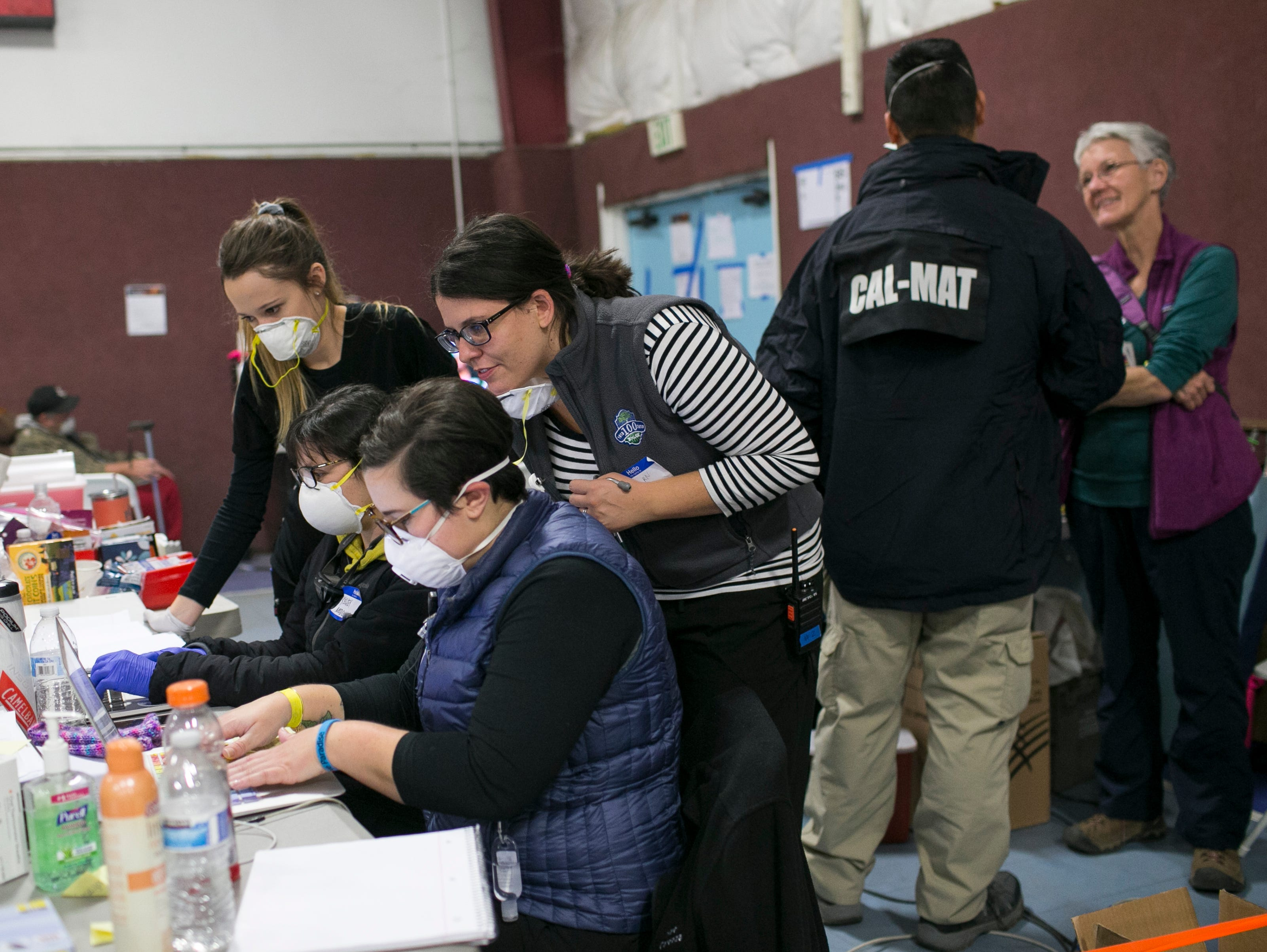 Nurses lean over the medical station inside the East Avenue Church Shelter in Chico, California on November 15, 2018. Less than a week after the Camp Fire destroyed the town of Chico, a rotational volunteer based nursing staff had joined the East Avenue Church shelter to lend a hand to the displaced evacuees seeking hosing there.