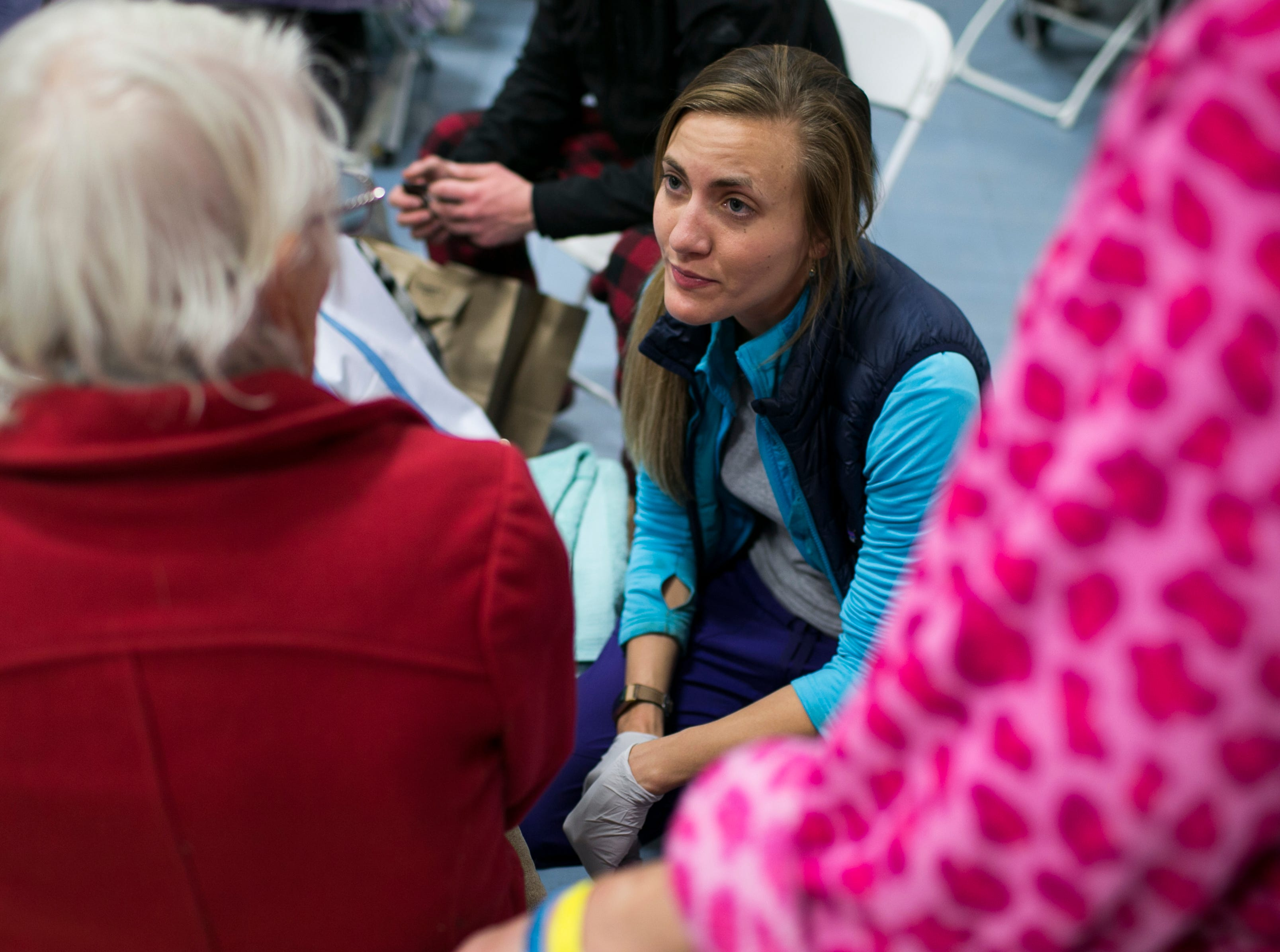 ER nurse Birgitte Randall (center)  speaks with an evacuee of the Paradise fire at the East Avenue Church Shelter in Chico, California on November 17, 2018. Randall fled her burning hospital Feather River in Paradise as the Camp Fire burned through town, eventually destroying her home. Responding to a Facebook request for help at the East Avenue Shelter, Randall and several of her colleagues and friends quickly sprung to action, starting a pop up clinic at the shelter to aid evacuees in need of medical attention.