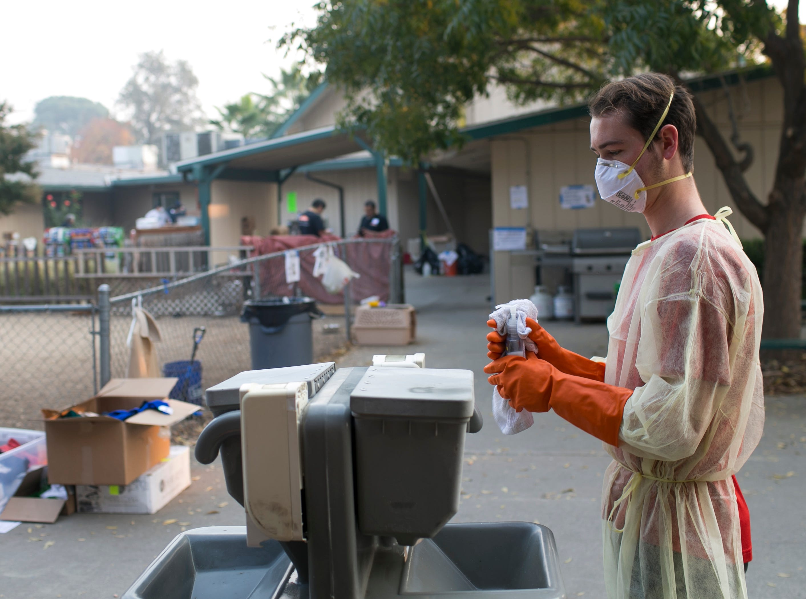 Volunteer Matt Negley washes down a soap station with bleach at the East Avenue Church shelter in Chico, California, on Nov. 17, 2018. Nearly a week after the Camp Fire burned through the town of Paradise, killing at least 84 and displacing thousands, several reports of Norovirus outbreak were reported at shelters across Chico.