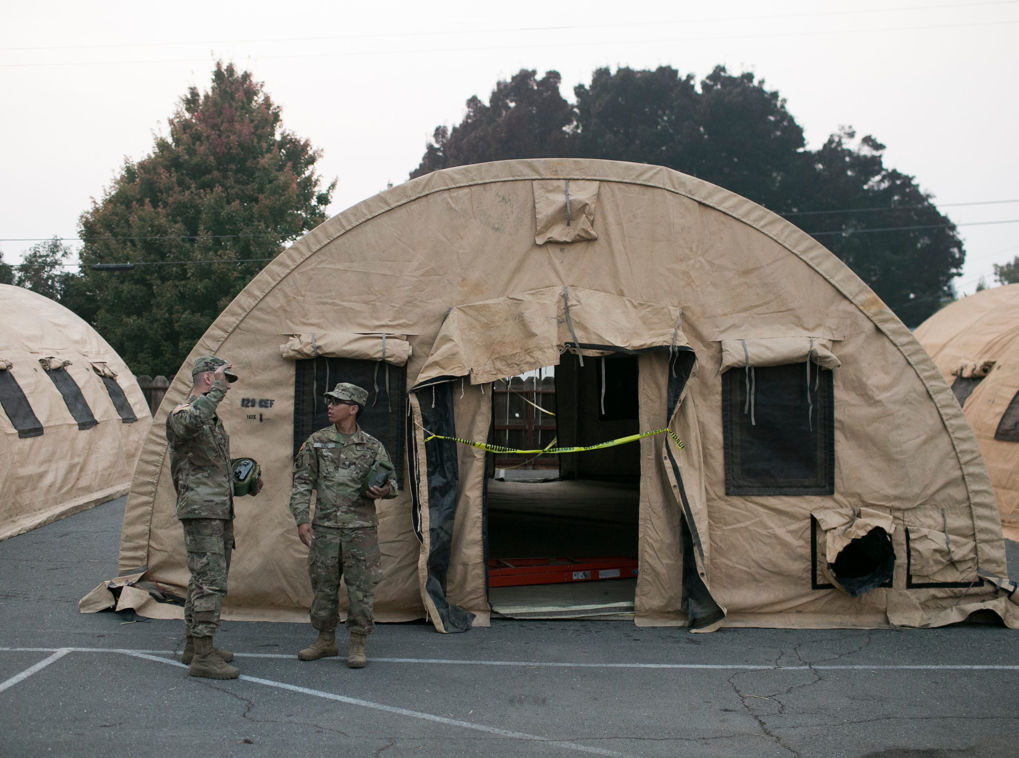 Members of the Air National Guard out of Fresno arrive at the East Avenue Church Shelter to help set up isolation tents in Chico, California on November 17, 2018. According to volunteers at the shelter, the isolation tents had been dropped off by government officials three days before but had not been set up. Nearly a full week after the shelter had opened the three tents sat empty and unusable.