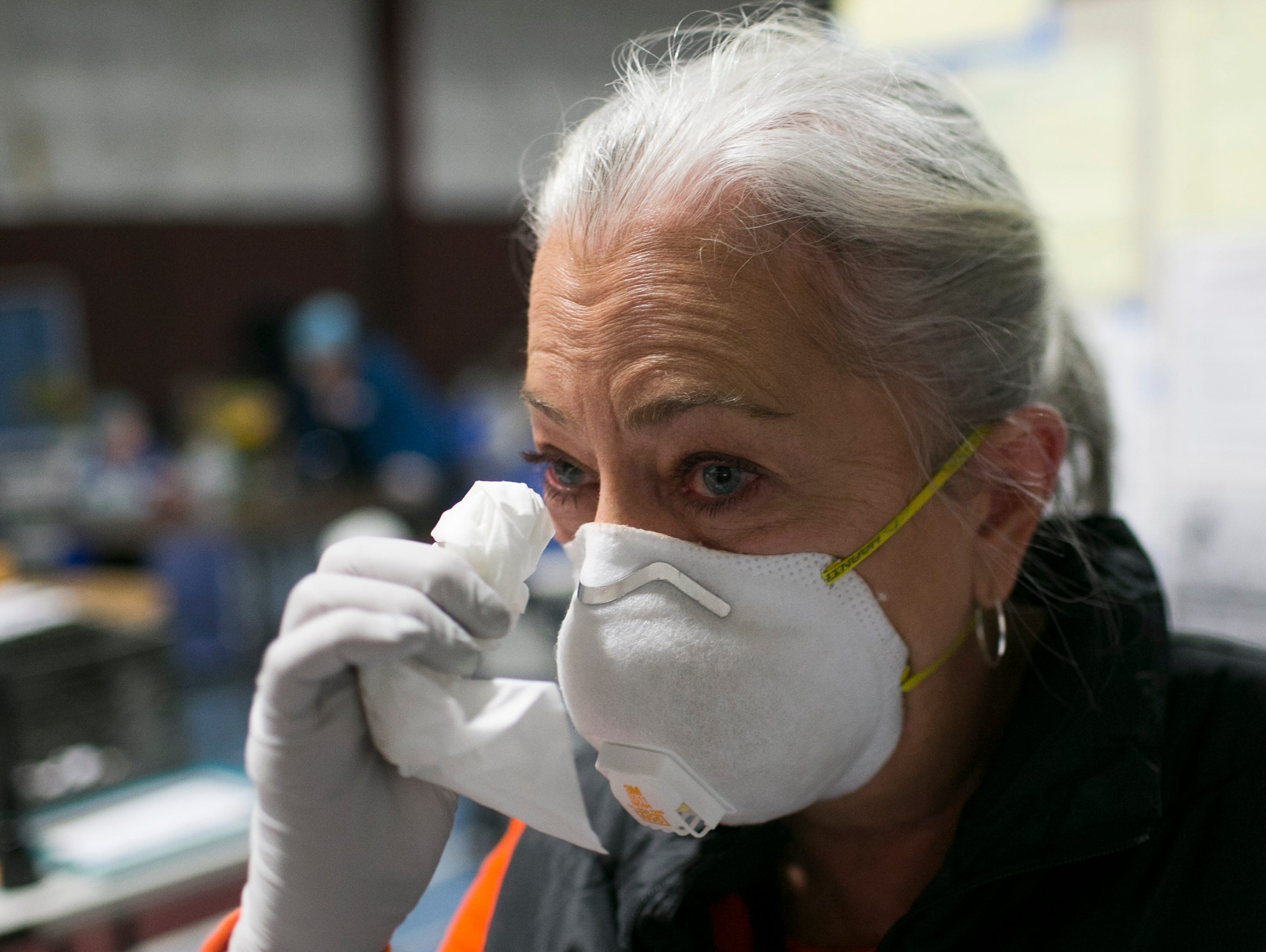 Kathleen Hassig wipes a tear from her eye after talking about her experience volunteering with Camp Fire evacuees at the East Avenue Church Shelter in Chico, California on November 16, 2018.