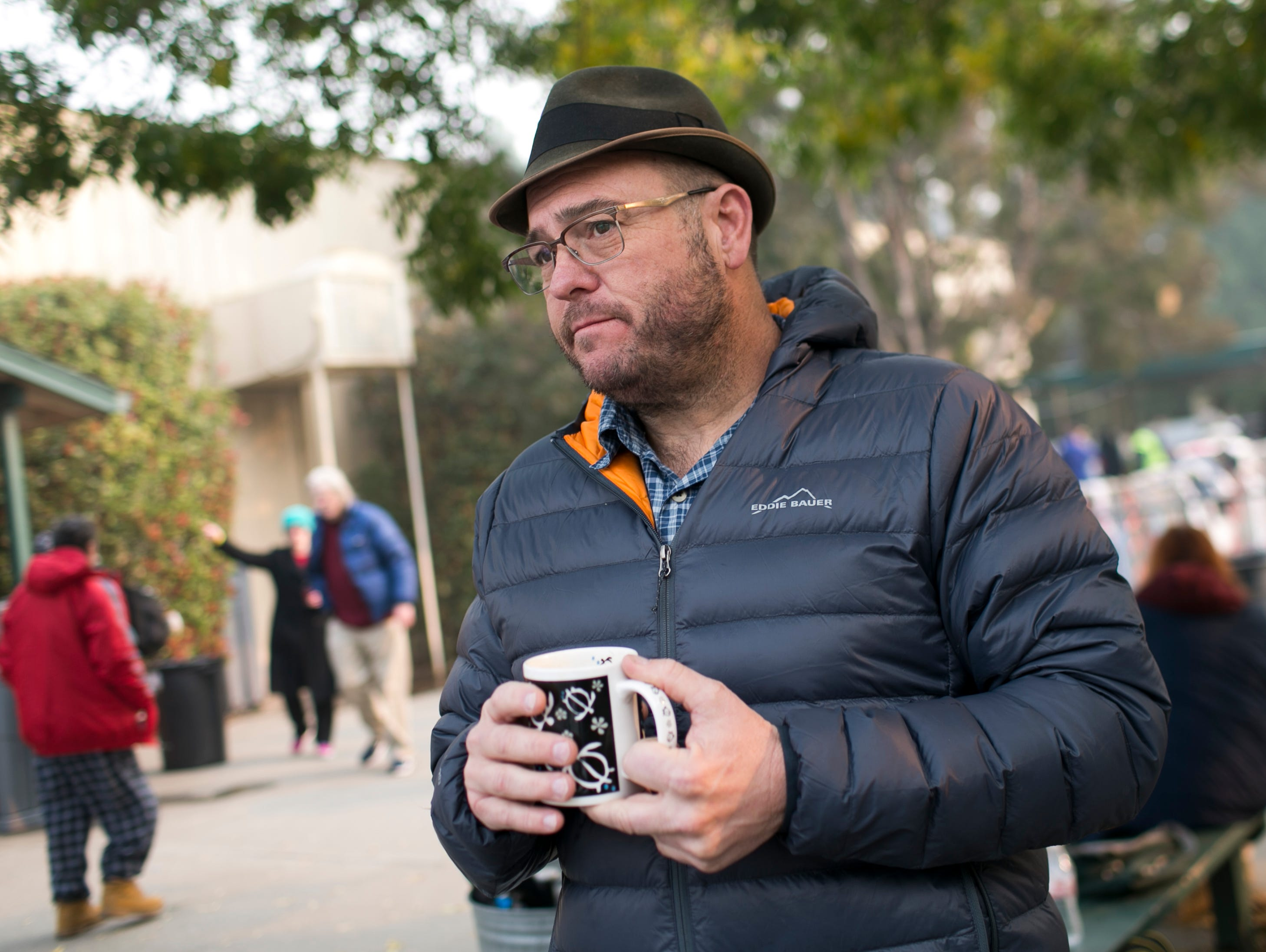 Pastor Ron Zimmer holds his morning coffee and stands outside the East Avenue Church Shelter in Chico, California on Nov. 17, 2018. Pastor Zimmer opened his church as a pop up shelter by the morning after the Camp Fire had burned through the town of Paradise, killing at least 80 and displacing thousands.