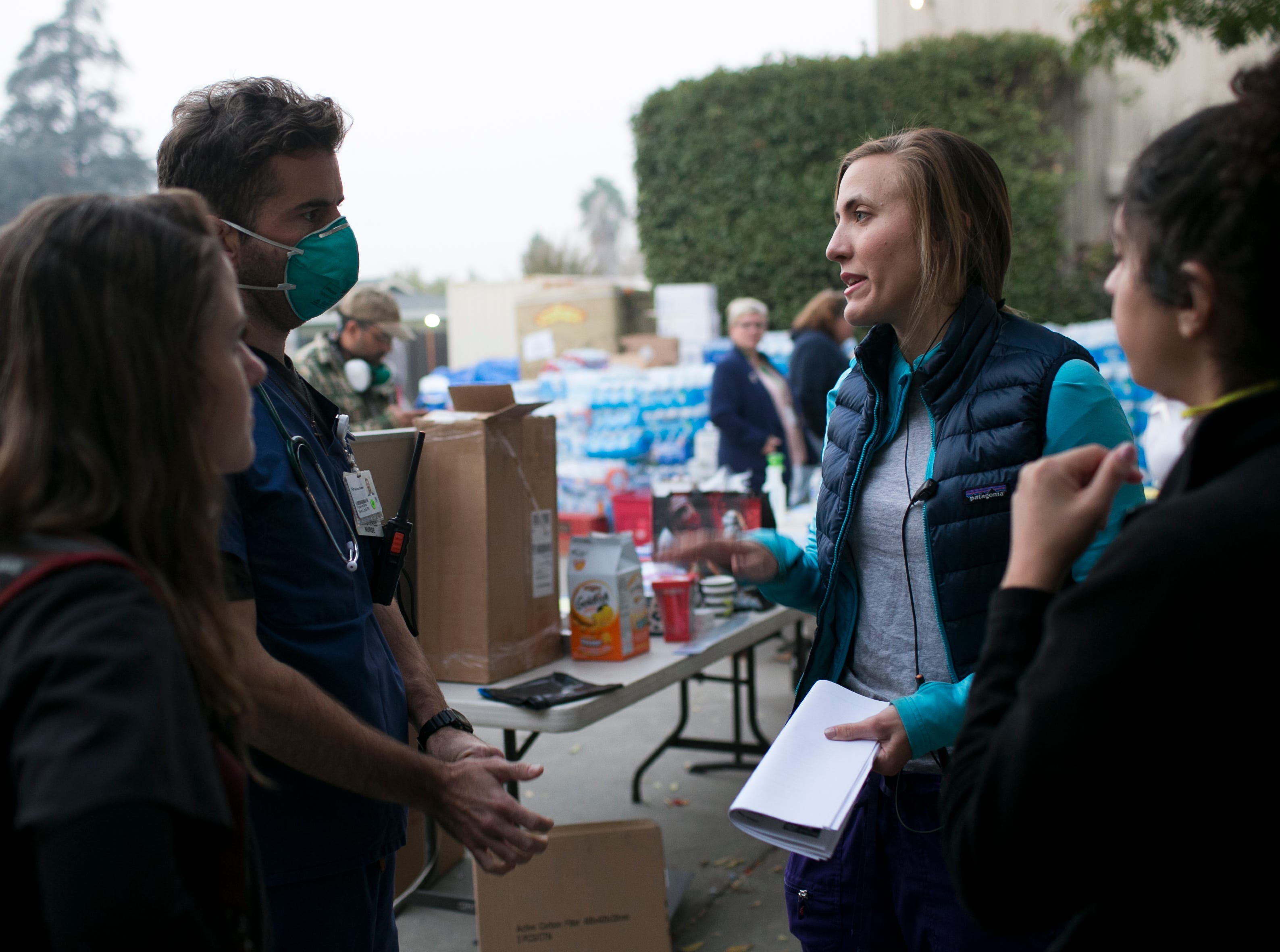 ER nurse Birgitte Randall (Center-right)  speaks with volunteer medical staff at the East Avenue Church Shelter in Chico, California on November 17, 2018. Randall fled her burning hospital Feather River in Paradise as the Camp Fire burned through town, eventually destroying her home. Responding to a Facebook request for help at the East Avenue Shelter, Randall and several of her colleagues and friends quickly sprung to action, starting a pop up clinic at the shelter to aid evacuees in need of medical attention.
