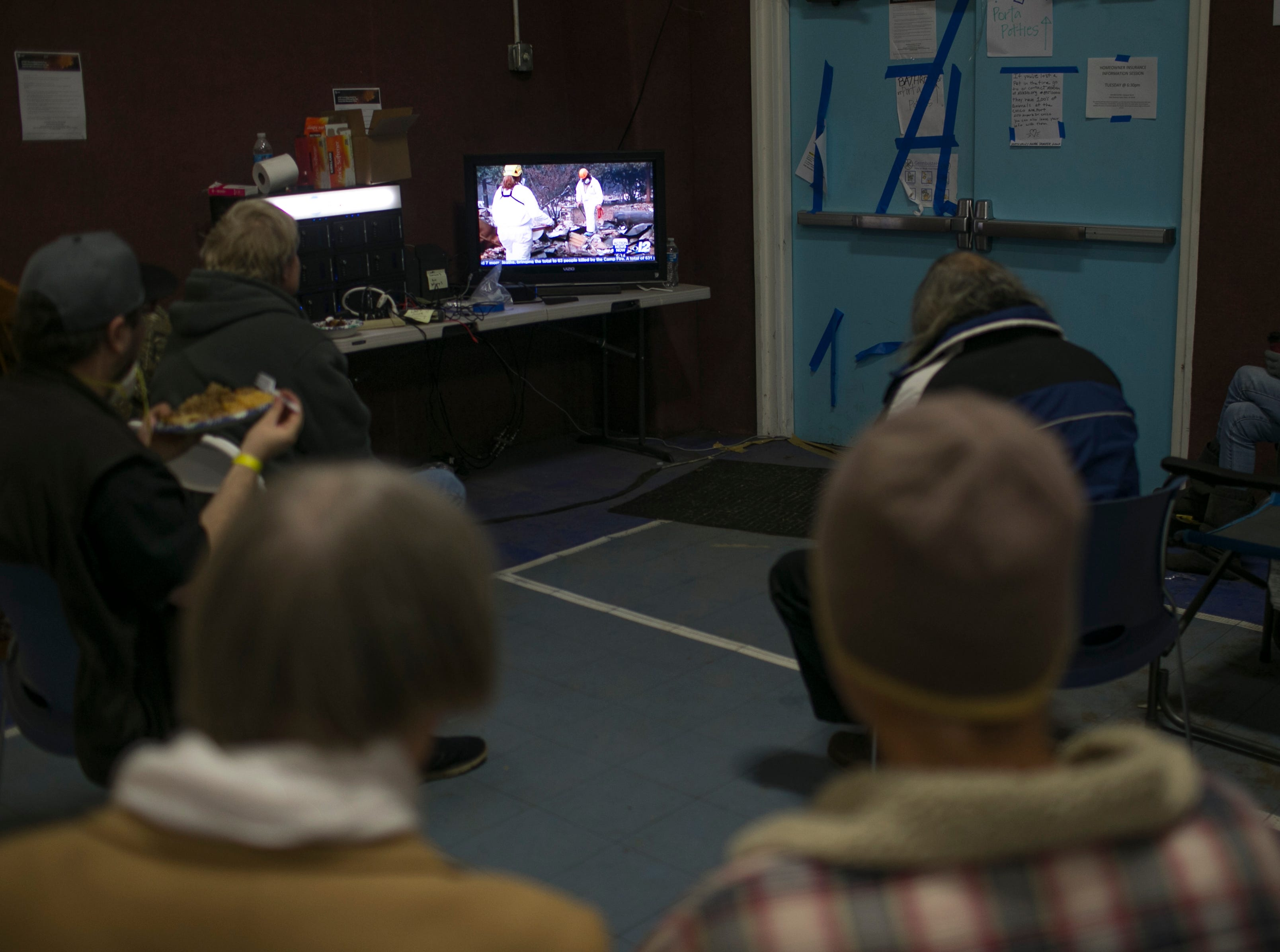 Camp Fire evacuees, many whom lost their homes and property in Paradise to the flames, watch as search teams look for human remains in Paradise on the news during dinner at the East Avenue Church Shelter in Chico, California on November 16, 2018.