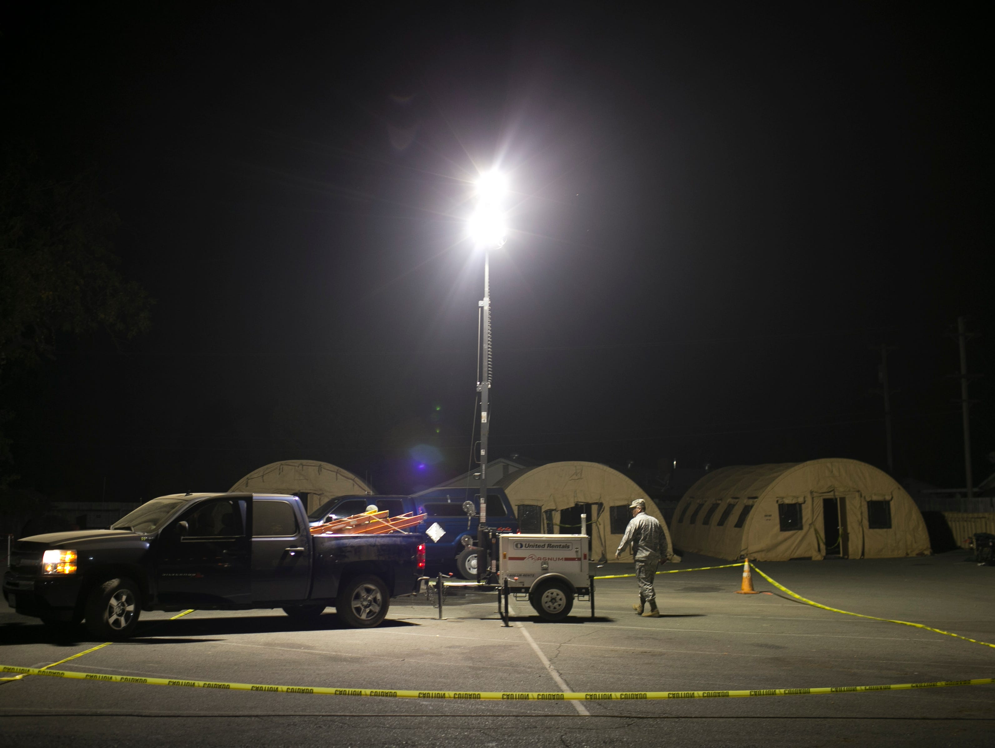 Members of the Air National Guard out of Fresno set up lights outside the East Avenue Church Shelter to help with working on isolation tents in Chico, California on November 17, 2018. According to volunteers at the shelter, the isolation tents had been dropped off by government officials three days before but had not been set up. Nearly a full week after the shelter had opened the three tents sat empty and unusable.